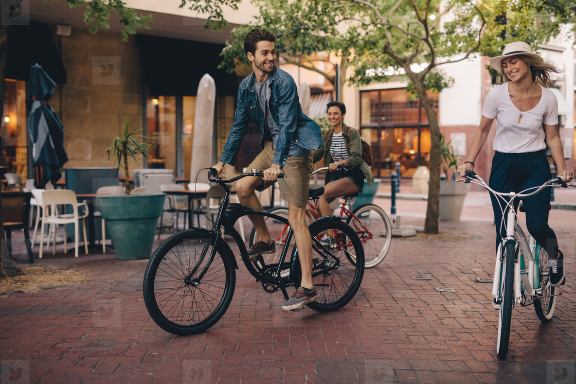Friends enjoying riding bicycles on city street