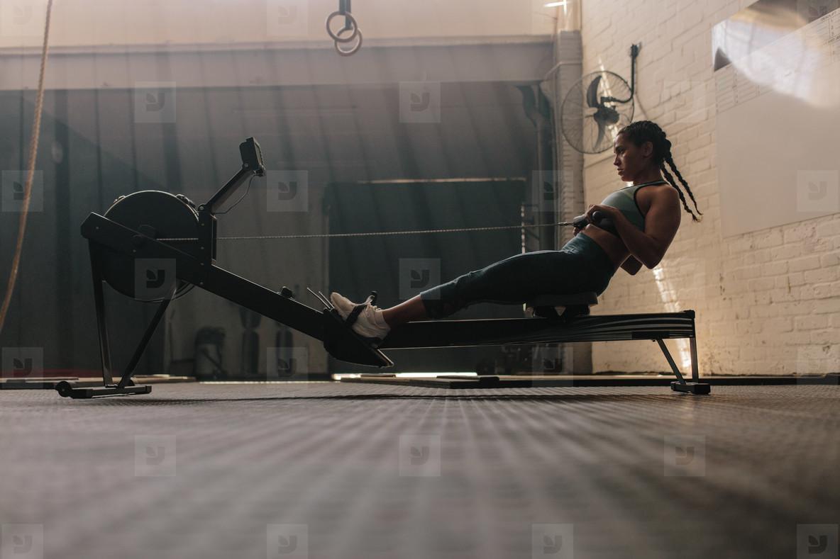 Female using rowing machine at health club
