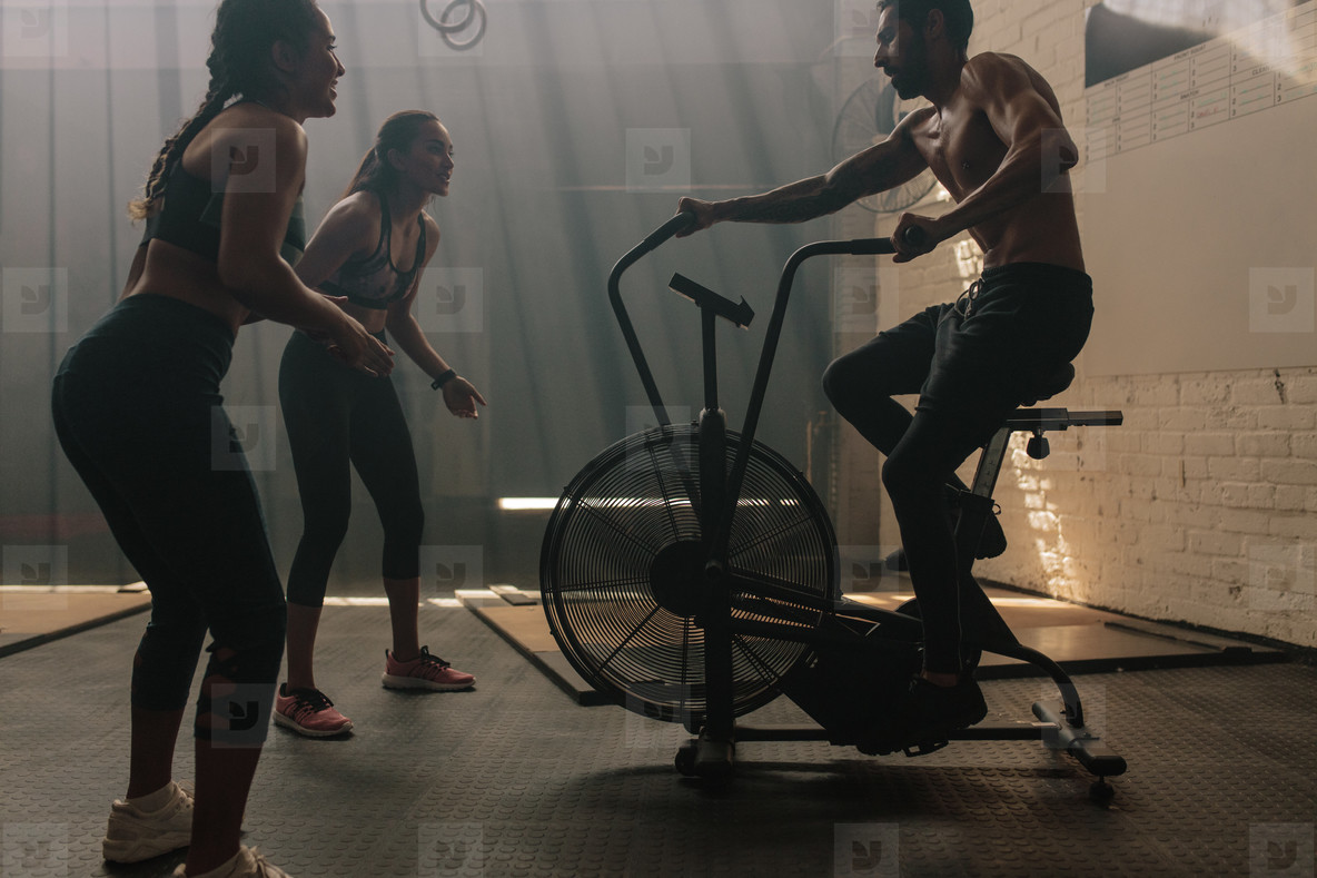 Two women motivating man exercising on air bike in gym