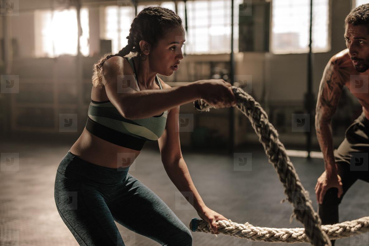 Female exercising with battle ropes