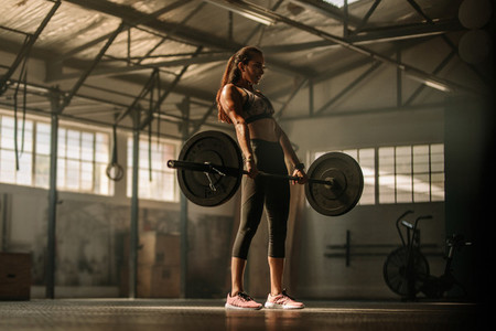Cross fit woman lifting heavy weights in gym