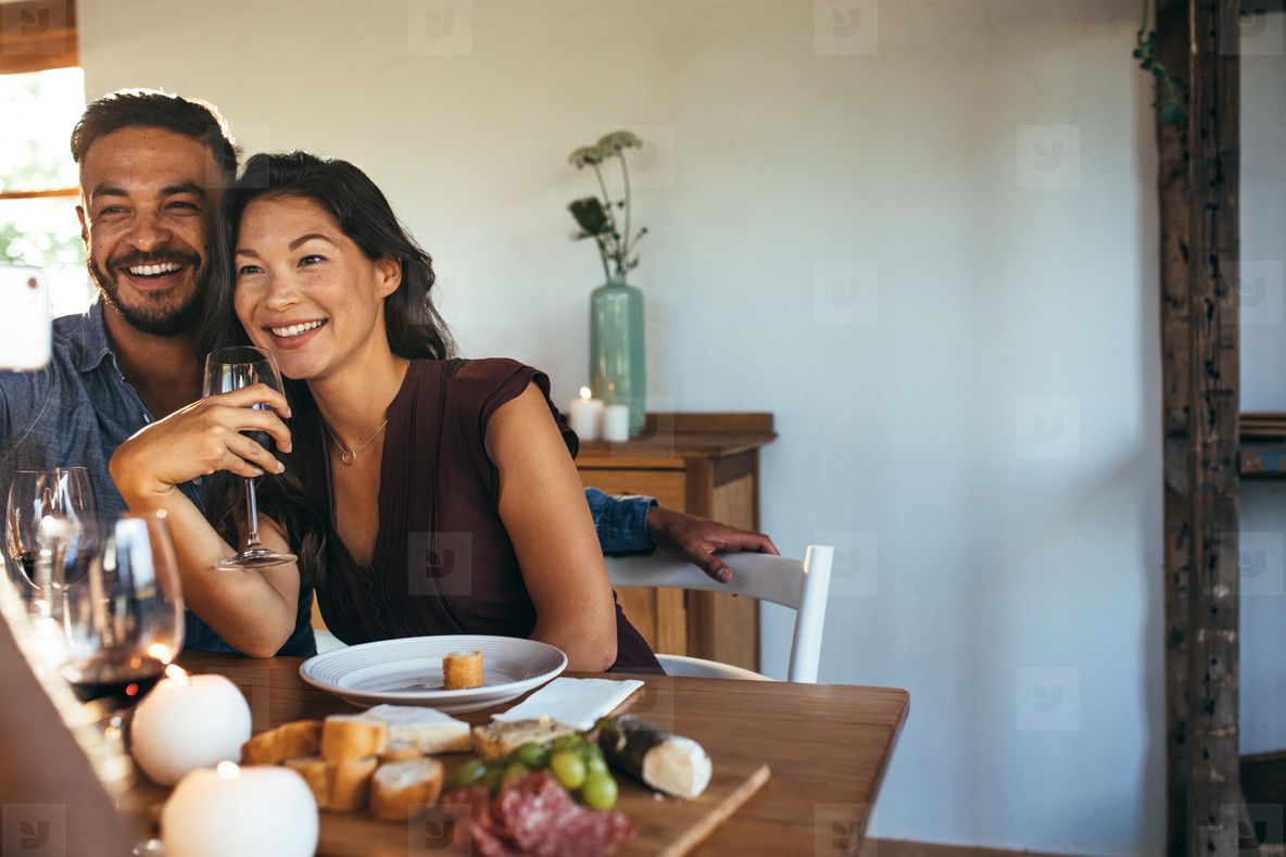 Couple having dinner party with friends taking selfie