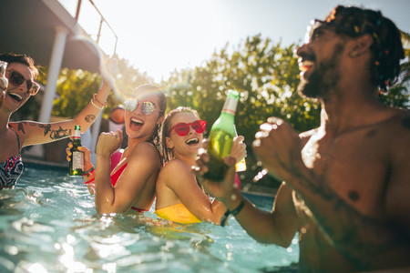Group of happy friends at pool party with beers