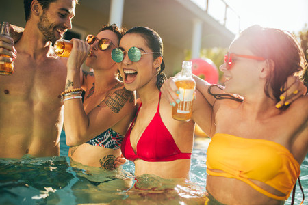 Group of friends partying in swimming pool