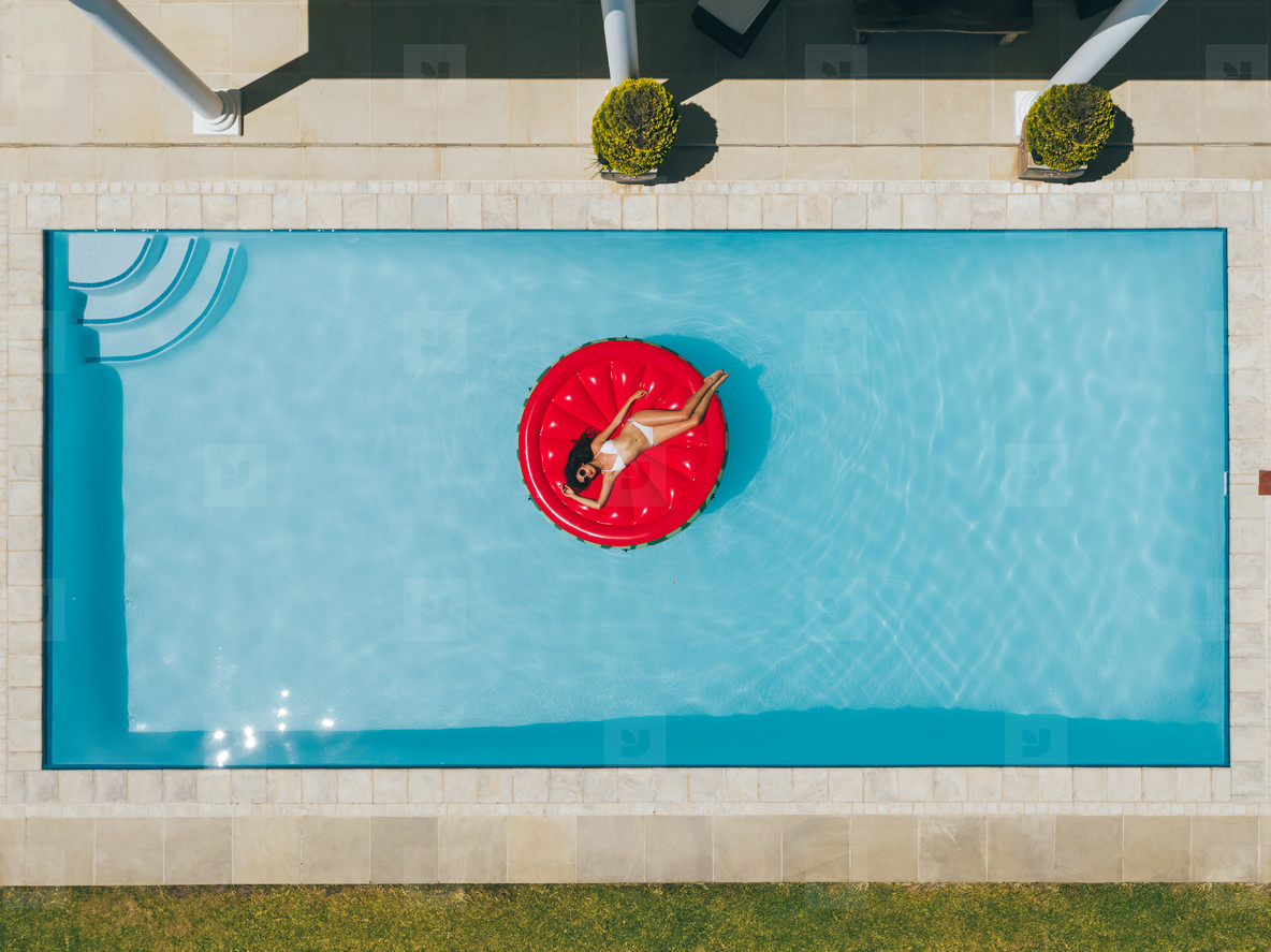 Woman floating on inflatable mattress in pool