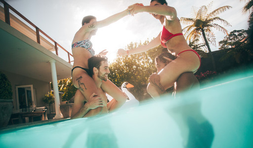 Women sitting on their boyfriends shoulders in pool