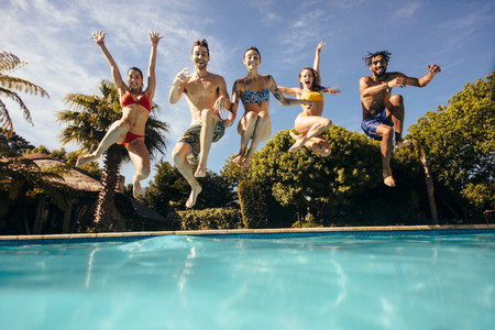 Crazy young people jumping into a pool