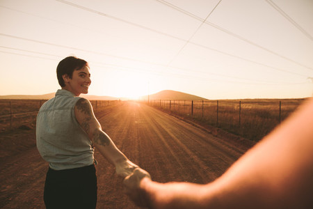 Couple walking hand in hand on highway
