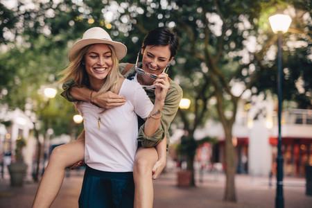 Women friends piggybacking and enjoying on city street