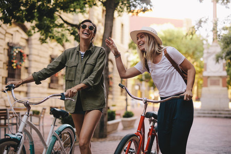 Women walking down the city street with their bicycles