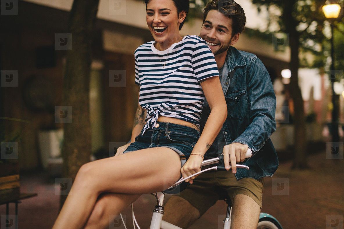 Couple having fun while riding bicycle