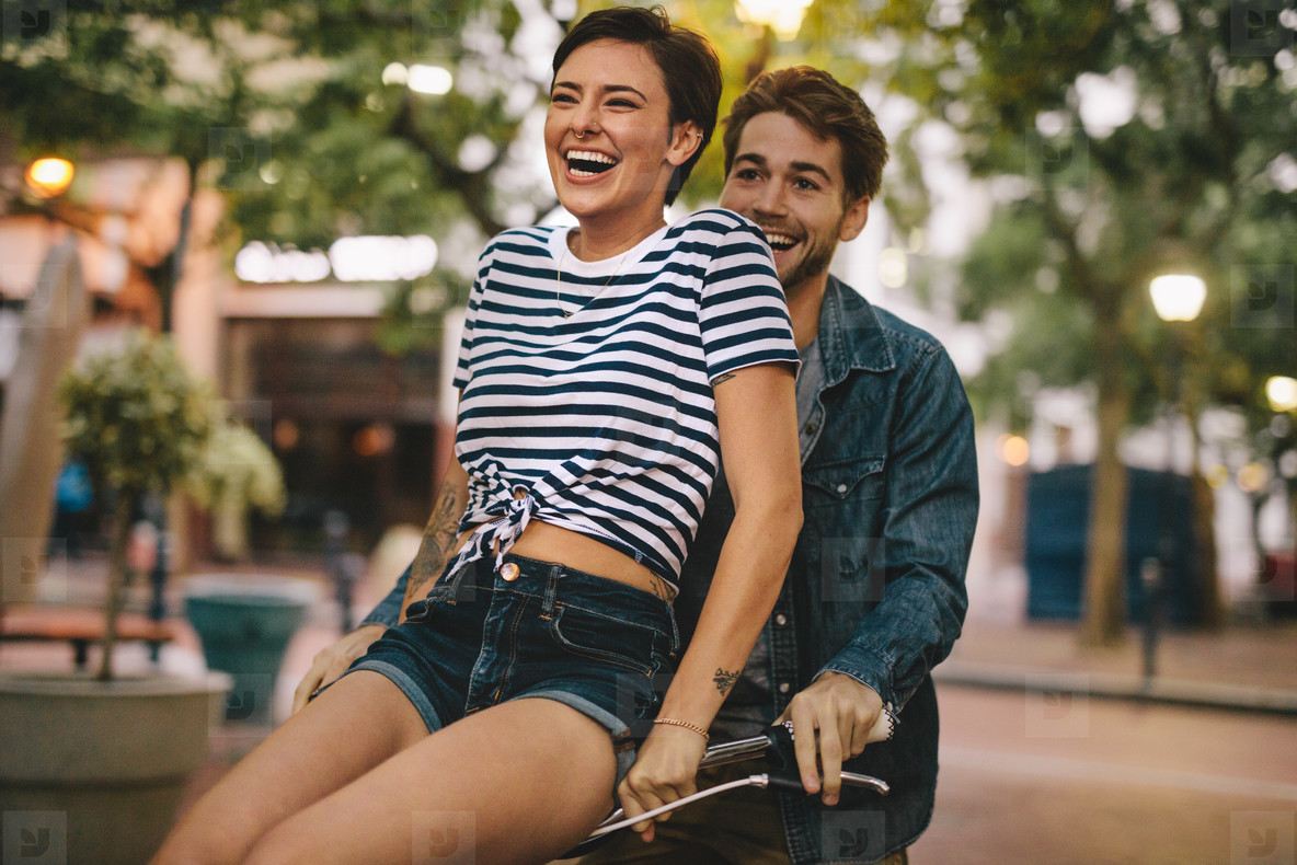 Happy couple on bicycle in the city