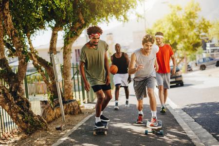 Men skating on skateboard on pavement