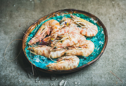 Raw uncooked tiger prawns on chipped ice fresh seafood