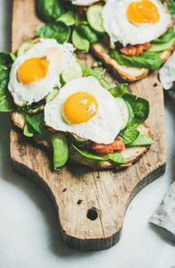 Healthy breakfast sandwiches on wooden board over grey background