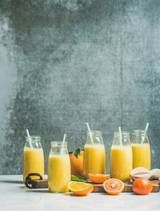 Healthy yellow smoothie over grey wall background copy space
