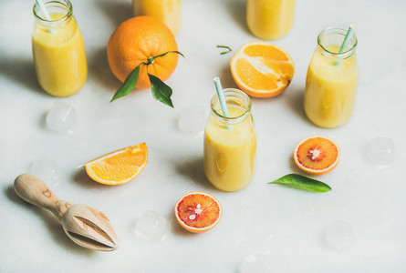 Healthy yellow smoothie with citrus fruit  marble background