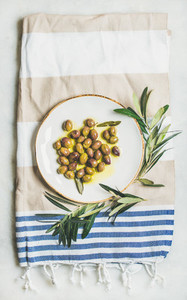 Pickled green Mediterranean olives on white ceramic plate  top view