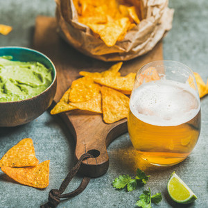Mexican corn chips  fresh guacamole sauce and beer  square crop