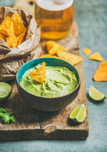 Fresh guacamole sauce in blue bowl and corn chips