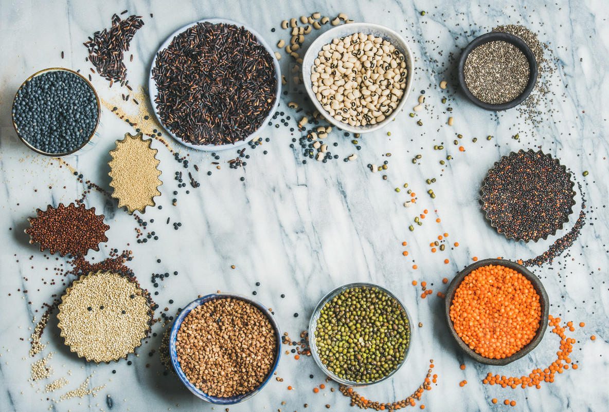Various raw uncooked grains  beans  cereals in bowls  copy space