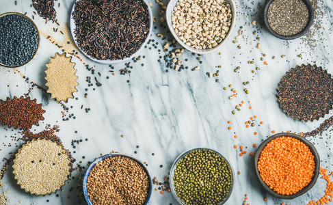 Various raw uncooked grains beans cereals in bowls and cups