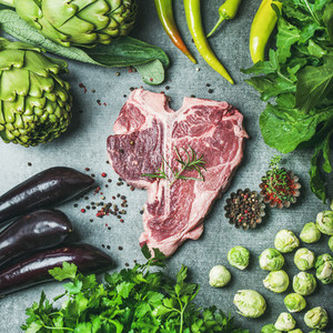 Raw beef t bone steak with vegetables and spices square crop