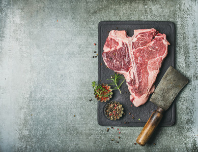 Fresh raw beef uncooked t bone steak with spices copy space