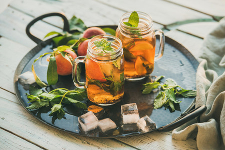 Summer refreshing cold peach ice tea on rustic wooden table