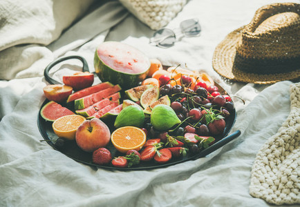 Tray full of fresh seasonal fruit over light blanket background