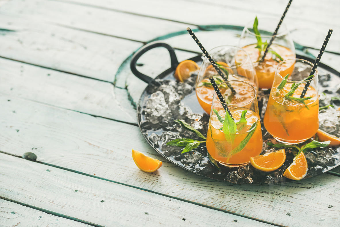 Refreshing alcoholic summer cocktail in glasses on tray  copy space