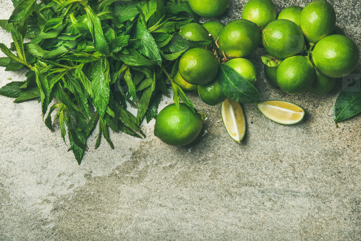 Flatlay of freshly picked limes and mint for making cocktail