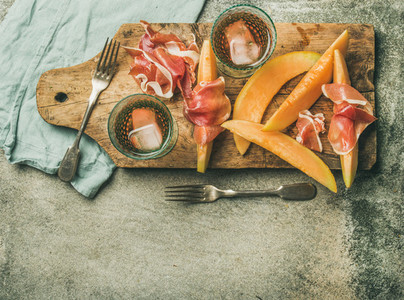 Flatlay of rose wine prosciutto ham melon copy space