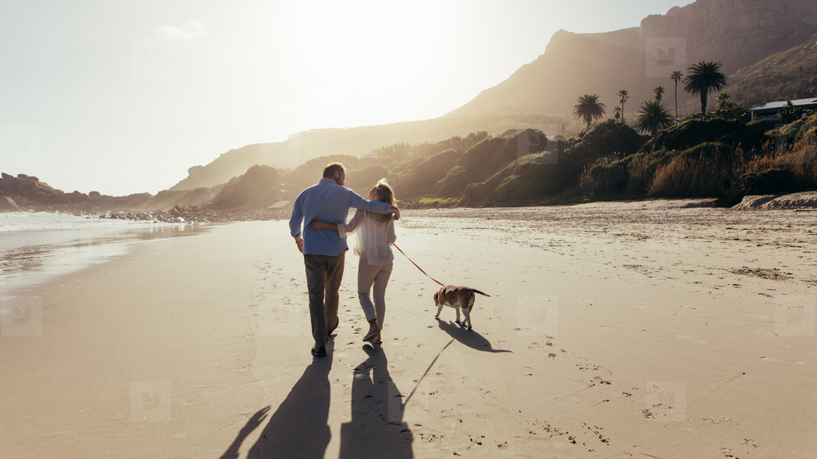 Mature couple strolling along the beach with dog