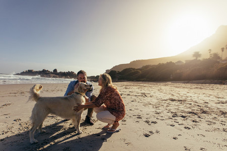 Senior couple with pet dog on beach