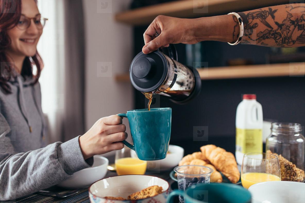 Boyfriend serving coffee to girlfriend