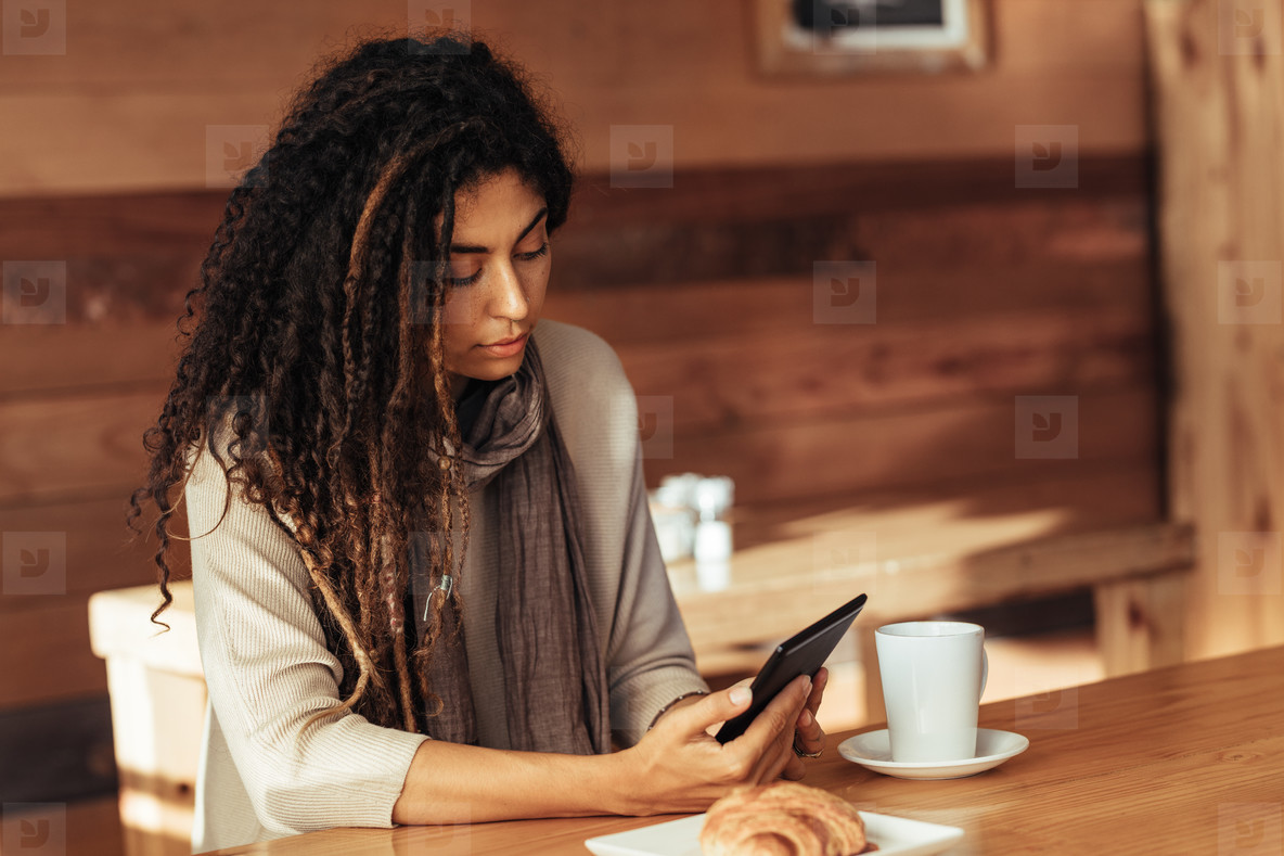 Woman sitting in a cafe looking at her mobile phone