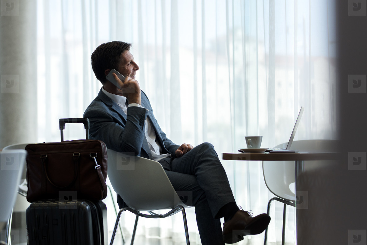 Businessman at airport lounge talking on phone
