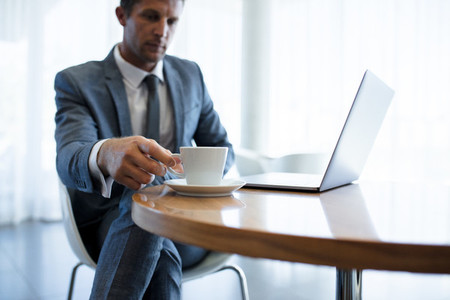 Businessman sitting at a table with laptop and coffee