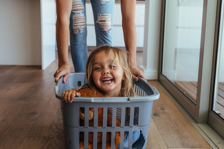 Little girl and her mother having fun doing laundry