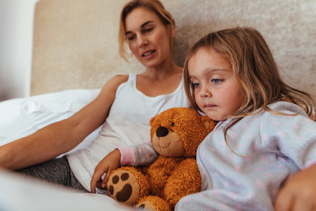Mother and daughter reading a book in bed