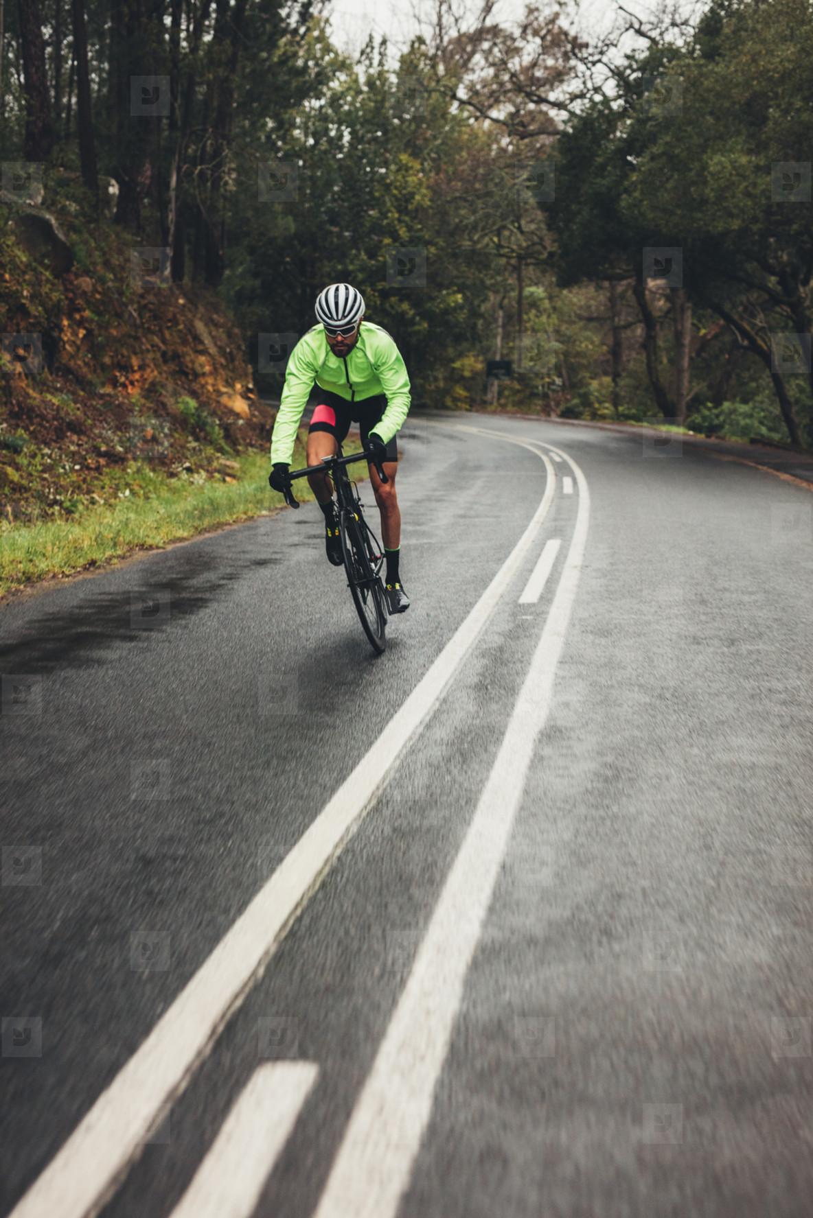 Bicycle rider with bike on wet asphalt road