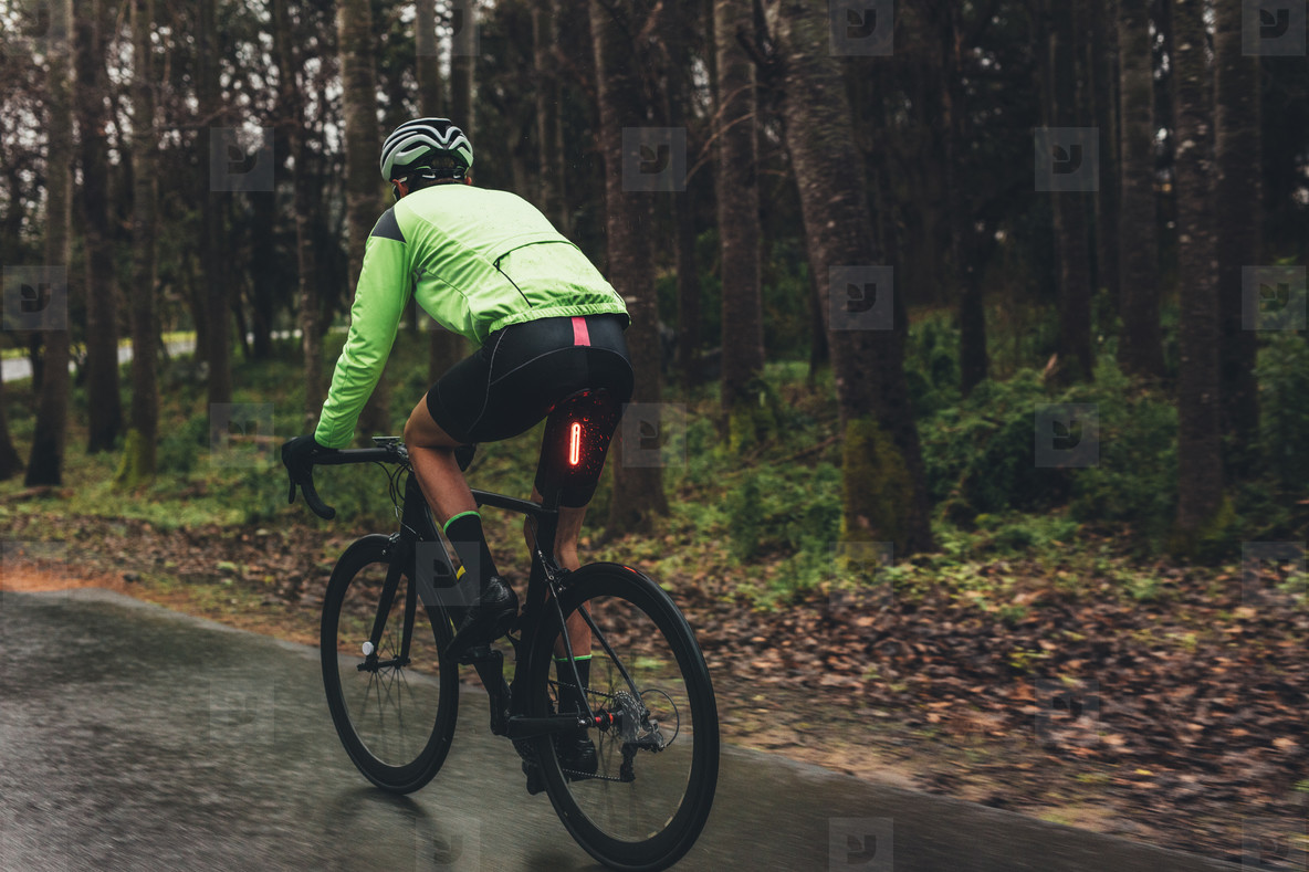 Male cyclist training on wet road