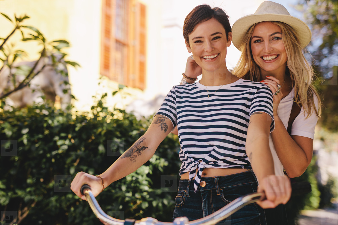 Best friends enjoying bicycle ride in the city