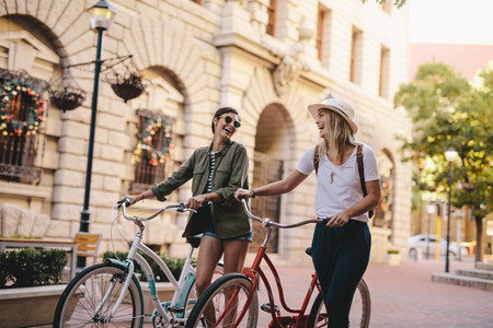 Friends walking with bicycles on street