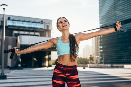 Smiling female athlete with skipping ropes