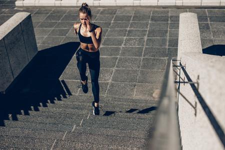 Sportswoman exercising on staircase