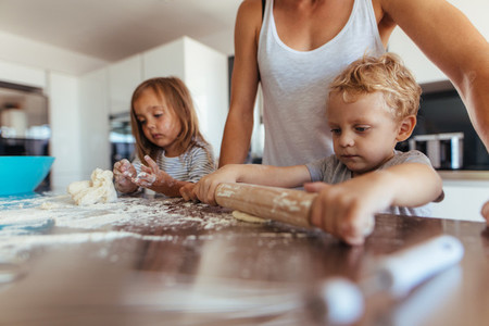 Kids making cookies with mother in kitchen