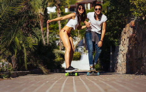 Happy couple riding on skateboards on vacation