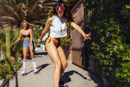 Female friends doing skateboarding on summer vacation